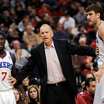 Philadelphia 76ers coach Doug Collins, center, hold back Spencer Hawes (00) and Royal Ivey as he talks to an official during the second half of an NBA basketball game against the Cleveland C …
