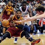 Cleveland Cavaliers' Kyrie Irving (2) turns the ball over as he falls in front of Philadelphia 76ers' Spencer Hawes (00) and Jrue Holiday (11) during the second half of an NBA basketball gam …