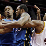 Washington Wizards' Kevin Seraphin, left, and Trevor Booker and Cleveland Cavaliers' Leon Powe struggle for a loose ball in the fourth quarter in an NBA preseason basketball game Thursday, O …