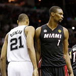 San Antonio Spurs' Tim Duncan (21) and Miami Heat's Chris Bosh (1) pass each other between plays during the first half at Game 5 of the NBA Finals basketball series, Sunday, June 16, 2013, i …
