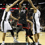 Miami Heat's Dwyane Wade (3) is defended by San Antonio Spurs' Tim Duncan, left, and Kawhi Leonard (2) during the first half at Game 5 of the NBA Finals basketball series, Sunday, June 16, 2 …
