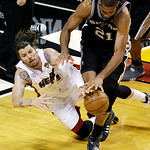 Miami Heat shooting guard Mike Miller (13) and San Antonio Spurs power forward Tim Duncan (21) vie for a loose ball during the second half of Game 6 of the NBA Finals basketball game, Tuesda …