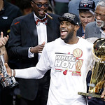 The Miami Heat's LeBron James, left, holding the  Larry O'Brien NBA Championship Trophy and his Bill Russell NBA Finals Most Valuable Player Award after Game 7 of the NBA basketball champion …