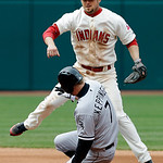 Cleveland Indians second baseman Ryan Raburn avoids Chicago White Sox's Jeff Keppinger (7) after throwing to first to complete a double play on Alex Rios in the sixth inning of a baseball ga …