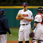 Cleveland Indians starting pitcher Justin Masterson, center, gets a visit from pitching coach Mickey Callaway, left, in the first inning of a baseball game against the Boston Red Sox Wednesd …