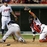 Cleveland Indians catcher Carlos Santana, right, holds the ball after Boston Red Sox's Mike Napoli scored on a single in the seventh inning of a baseball game Thursday, April 18, 2013, in Cl …