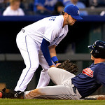 Cleveland Indians' Yan Gomes slides safely into third as the ball gets past Kansas City Royals third baseman Mike Moustakas (8) in the fourth inning of their second baseball game of a double …