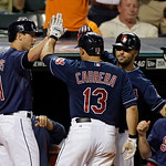 Cleveland Indians' Drew Stubbs, left, congratulates Asdrubal Cabrera (13) with Nick Swisher, second from right, after Stubbs scored on Cabrera's sacrifice fly in the eighth inning of a baseb …
