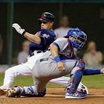 Cleveland Indians' Asdrubal Cabrera slides past Toronto Blue Jays catcher J.P. Arencibia to score on a single by Nick Swisher in the fourth inning of a baseball game Tuesday, July 9, 2013, i …