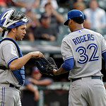 Toronto Blue Jays catcher Josh Thole, left, talks to relief pitcher Esmil Rogers (32) in the second inning of a baseball game against the Cleveland Indians Wednesday, July 10, 2013, in Cleve …