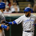 Toronto Blue Jays' Emilio Bonifacio, right, celebrates with Colby Rasmus after both scored on a single by Munenori Kawasaki in the ninth inning of a baseball game against the Cleveland India …