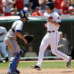Cleveland Indians' Drew Stubbs, right, scores on a triple by Carlos Santana in the eighth inning of a baseball game, as Toronto Blue Jays catcher Josh Thole watches, Thursday, July 11, 2013, …