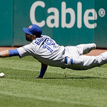 Toronto Blue Jays right fielder Jose Bautista dives for an rbi triple hit by Cleveland Indians' Carlos Santana in the eighth inning of a baseball game, Thursday, July 11, 2013, in Cleveland. …