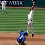 Kansas City Royals center fielder Lorenzo Cain, left, steals to second base as Cleveland Indians' Mike Aviles jumps high but cannot catch the ball in the fourth inning of a baseball game, Su …