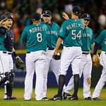 Seattle Mariners catcher Mike Zunino, left, Kendrys Morales (8), and Tom Wilhelmsen (54) are greeted by teammates after the Mariners beat the Cleveland Indians 2-1 in a baseball game, Monday …