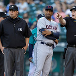 Cleveland Indians bench coach Sandy Alomar, Jr., second from right, listens to home plate umpire Bill Welke, right, as umpire Lance Barrett, second from left, during a conference prior to a  …