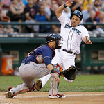 Seattle Mariners' Kendrys Morales, right, slides toward home as Cleveland Indians catcher Yan Gomes waits for the ball in a baseball game Tuesday, July 23, 2013, in Seattle. (AP Photo/Elaine …