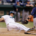 Seattle Mariners' Kendrys Morales slides across the plate after being tagged out by Cleveland Indians catcher Yan Gomes in the third inning of a baseball game Tuesday, July 23, 2013, in Seat …