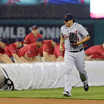 Detroit Tigers left fielder Matt Tuiasosopo runs for the dugout as the grounds crew rolls out the tarp as rain delays a baseball game between the Tigers and Cleveland Indians in the second i …
