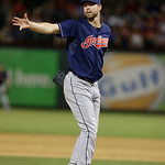 Cleveland Indians starting pitcher Corey Kluber tries to bare-hand catch the infield hit by Texas Rangers Elvis Andrus during the eighth  inning of a baseball game Tuesday, June 11, 2013, in …