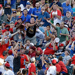 Spectators reach for a foul ball hit into the stands during the baseball game between the Cleveland Indians and Texas Rangers Wednesday, June 12, 2013, in Arlington, Texas. (AP Photo/LM Oter …