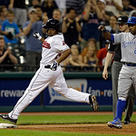 Cleveland Indians' Michael Bourn arrives at third base as Kansas City Royals third baseman Miguel Tejada (24) on a wild pitch by relief pitcher Greg Holland in the ninth inning of a baseball …