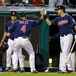 Cleveland Indians' Lonnie Chisenhall, right, greets Mike Aviles (4) at the dugout after Aviles scored the go ahead run against the Kansas City Royals in the eighth inning of a baseball game  …