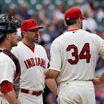 Cleveland Indians pitching coach Mickey Callaway, center, visits starting pitcher Zach McAllister (34) and catcher Yan Gomes in the third inning of a baseball game against the Tampa Bay Rays …