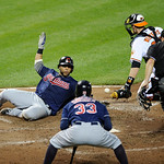 Cleveland Indians' Carlos Santana, left, slides home to score on a single by Michael Brantley against Baltimore Orioles catcher Matt Wieters, right, during the sixth inning of a baseball gam …