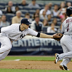 New York Yankees third baseman David Adams, left, tags out Cleveland Indians' Mike Aviles in a rundown on a ball hit by Nick Swisher during the third inning of a baseball game at Yankee Stad …