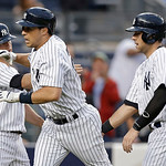 New York Yankees' Brett Gardner, left, and Austin Romine, right, celebrate with Mark Teixeira after Texeira's third-inning grand slam off Cleveland Indians starting pitcher Justin Masterson  …