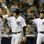 New York Yankees Mark Teixeira (25), left,  greets Austin Romine and New York Yankees right fielder Ichiro Suzuki after they scored on Brett Gardner's sixth-inning, two-run single in a baseb …