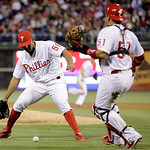 Philadelphia Phillies relief pitcher Antonio Bastardo, left, and catcher Carlos Ruiz cannot reach a single by Cleveland Indians' Michael Bourn in the seventh inning of a baseball game, Tuesd …