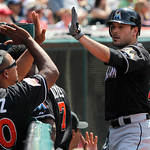 Miami Marlins' Greg Dobbs is congratulated at the dugout after scoring on a double by teammate Logan Morrison against the Cleveland Indians in the eighth inning of an interleague baseball ga …