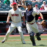 With Indians starting pitcher Derek Lowe watching, Cleveland Indians catcher Lou Marson throws out Miami Marlins' Bryan Petersen at first after a bunt in the first inning of an interleague b …