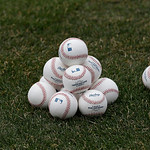 Baseballs are stacked on the field before the Cleveland Indians play the New York Yankees in a home opener baseball game, Monday, April 8, 2013, in Cleveland. (AP Photo/Tony Dejak)