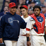 Cleveland Indians manager Terry Francona, left, walks off the field with Carlos Santana after Santana was hurt in the ninth inning of a home opener baseball game, Monday, April 8, 2013, in C …