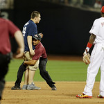 National League's Brandon Phillips, of the Cincinnati Reds, watches as a security guard tries to lift a spectator after he ran on the field during the fifth inning of the MLB All-Star base …