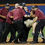 A spectator is carried by security personnel after he ran onto the field during the fifth inning of the MLB All-Star baseball game, on Tuesday, July 16, 2013, in New York. (AP Photo/Matt Slo …