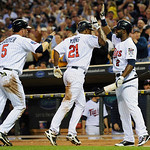 Minnesota Twins' on-deck batter Denard Span, right, congratulates Delmon Young, center, and Michael Cuddyer after they scored in the third inning on two throwing Cleveland Indians pitcher Ju …