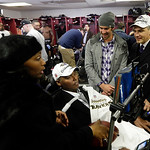 Former Baltimore Raven O.J. Brigance, center, his wife Chanda, left, and former Olympic swimmer Michael Phelps, second from right, visit the Ravens locker room after the NFL football AFC Cha …