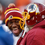 Injured Washington Redskins quarterback Robert Griffin III laughts with his teammates on the bench in the third quarter of an NFL football game against the Cleveland Browns in Cleveland, Sun …