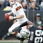 Cleveland Browns quarterback Brandon Weeden (3) scrambles Oakland Raiders defensive end Lamarr Houston (99) during the first half of an NFL football game in Oakland, Calif., Sunday, Dec. 2,  …