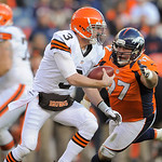 Cleveland Browns quarterback Brandon Weeden tries to get away from the rush of Denver Broncos defensive tackle Justin Bannan (97) during the second half  of an NFL football game, Sunday, Dec …