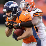 Denver Broncos wide receiver Brandon Stokley (14) tries to break a tackle by Cleveland Browns cornerback Trevin Wade (26) in the fourth quarter of an NFL football game, Sunday, Dec. 23, 2012 …