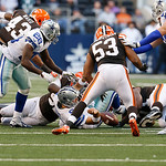 Dallas Cowboys quarterback Tony Romo (9) fumbles as Cleveland Browns linebacker Craig Robertson (53) looks to recover the ball during the second half of an NFL football game Sunday, Nov. 18, …