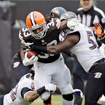 Cleveland Browns running back Trent Richardson, center, istackledd by Baltimore Ravens cornerback Jimmy Smith, left, and linebacker Terrell Suggs on a 9-yard run in the first quarter of an N …