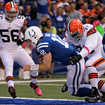 Indianapolis Colts' Andrew Luck (12) goes in for a three-yard touchdown run against Cleveland Browns' Ahtyba Rubin (71) and Kaluka Maiava (56) during the first half of an NFL football game S …