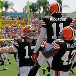 Cleveland Browns quarterback Jake Delhomme (17) rushes in to celebrate with teammates Mohamed Massaquoi (11) and Lawrence Vickers (47) after throwing a first quarter touchdown pass to Massaq …