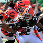 Cleveland Browns running back Trent Richardson (33) is tackled by Cincinnati Bengals linebacker Vincent Rey (57) and free safety Reggie Nelson (20) in the first half of an NFL football game, …
